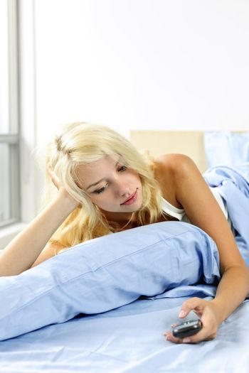 Woman dialing phone in bed
