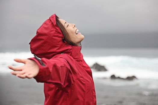 Rain. Woman enjoying a grey rainy fall day on the beach. Young smiling woman in red raincoat.