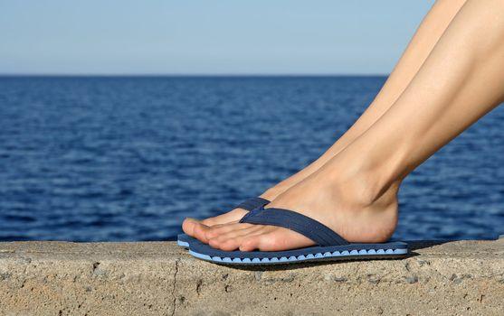 Female feet wearing blue flip-flops