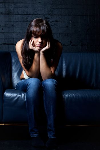 woman on a leather couch in despair