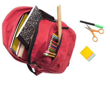 Bright red nylon backpack full of books, colored pencils, and with felt marker, sticky notes and scissors in front. All isolted on white for easy removal.