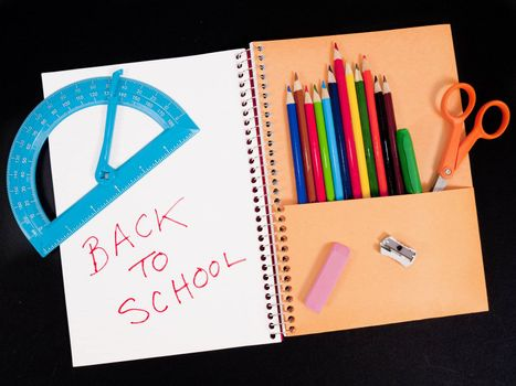 Back-to-school theme of student notebook with pocket full of colored pencils. Other items are scissors, protractor, sharpener, and eraser. Background is black.