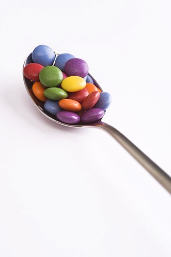 spoon with colorful sweets over white background