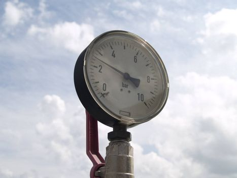Pressure meter on sky background, photographed on roof of the building