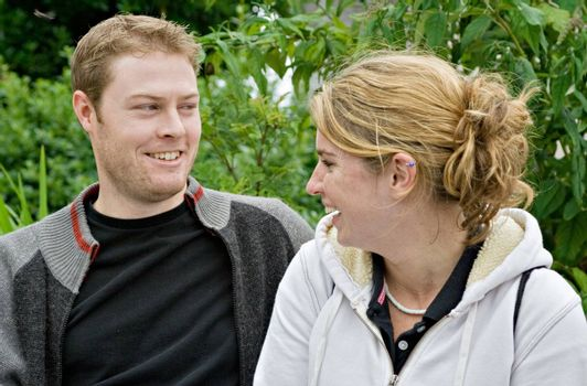A young man and young woman talking and laughing. They are enjoying each others company.