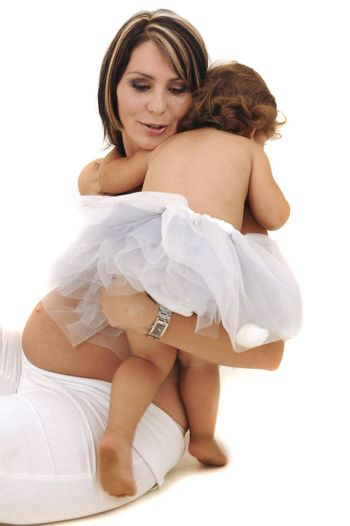 beautiful pregnant topless mother playing with her infant daughter