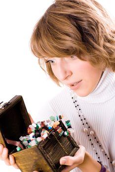 beautiful girl looks at wooden jewelry box