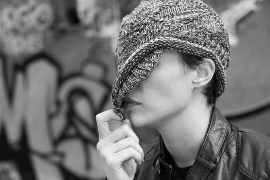 Woman hiding behind her cap