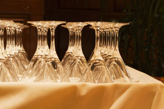 Crystal glassware is lined up on linen tablecloth in preparation for an elegant celebration;
