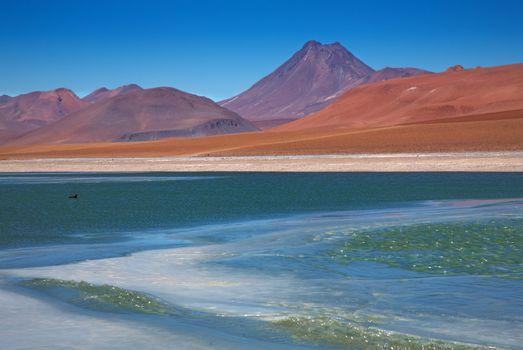 view on frozen lagoon Quepiaco and volcano Acamarachi in Atacama desert, Chile