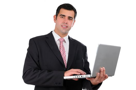 porPortrait of a confident young businessman in a dark suit holding laptop isolated on white