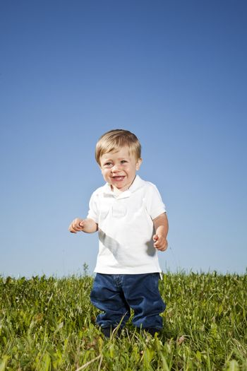 Young boy standing in the grass