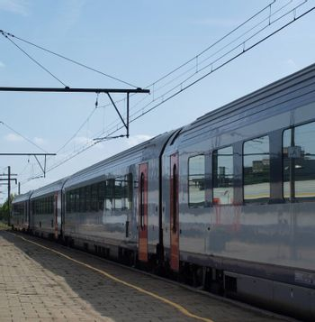 Electric passenger train arriving on an empty station platform