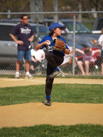 little league baseball pitcher throwing the ball on the mound