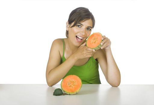 Beautiful young woman eating a cantaloupe