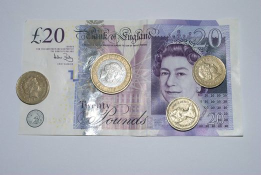 Twenty pound note with coin on top