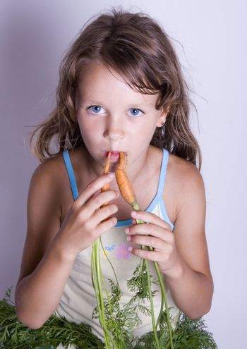 A sweet young girl eating fresh carrot. The child is on a white background