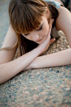 Woman lying on asphalt