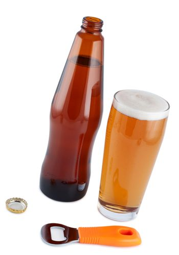 Beer in bottle with bottle opener and glass.