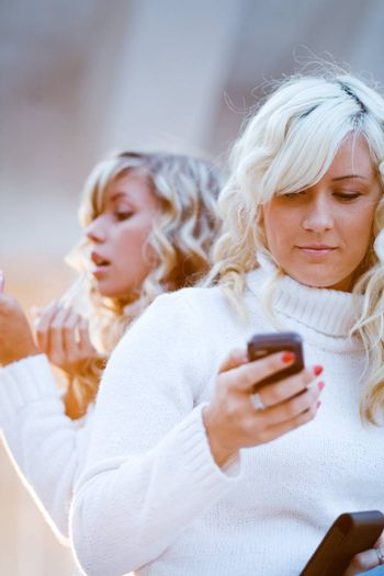 Two teenage girls watching mobile phone and makeup.