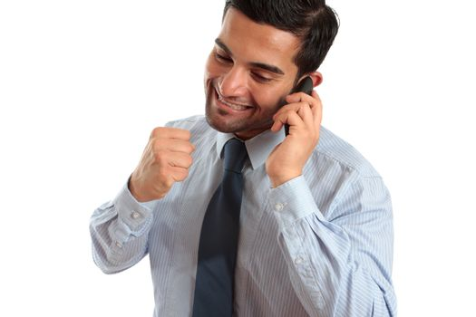 A very happy businessman or salesman on a telephone call and making a fist of success or achievement.  Sales deal, new job, promotion etc.