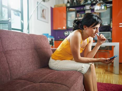 mid adult woman on sofa staring at her mobile phone and biting nails. Horizontal shape, full length, copy space