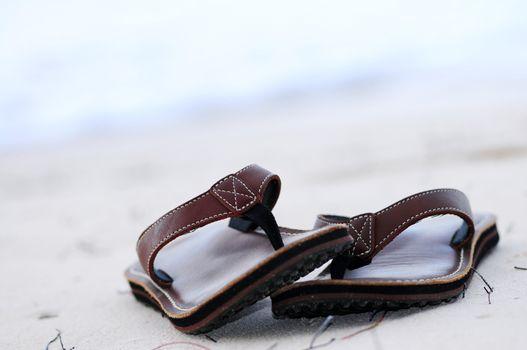 Flipflops on a sandy ocean beach - summer vacation concept