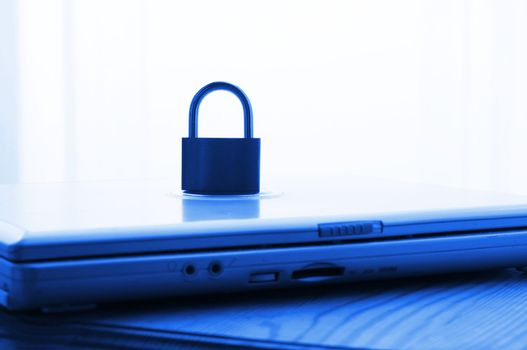 notebook and padlock showing internet or data security concept in blue