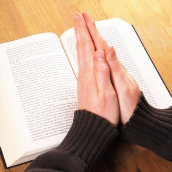 praying hand and book on desk showing religion concept