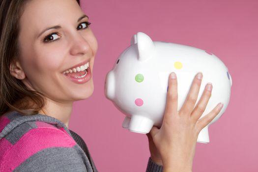 Pretty girl holding piggy bank