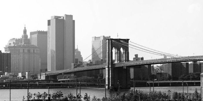 A wide angle panoramic view of the New York City skyline including the Brooklyn bridge and the Manhattan skyline.