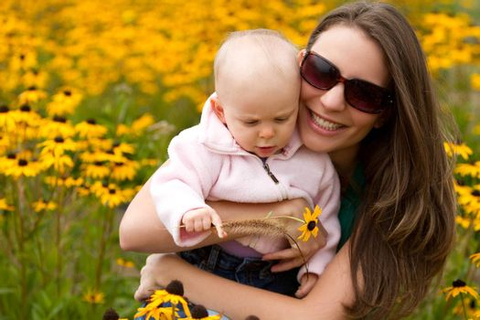 Beautiful smiling mother holding daughter