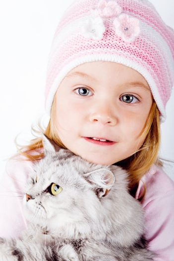 Lovely little girl with kitten on white background studio shot