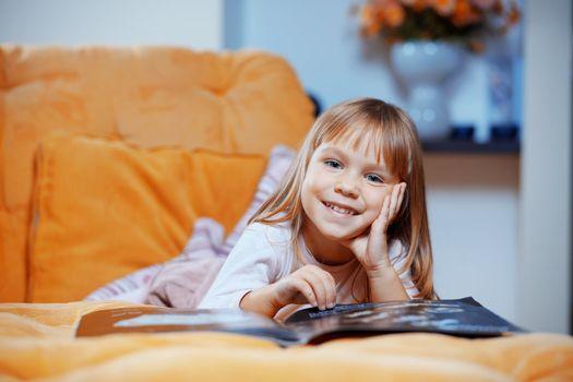 Child reading magazine on sofa