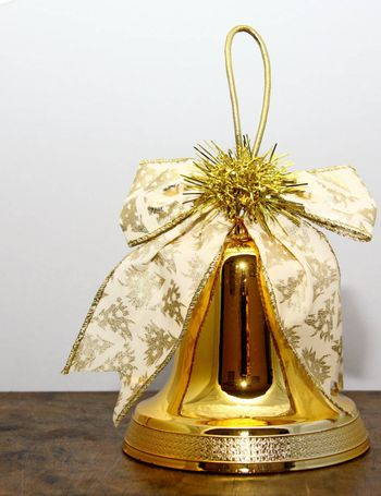 golden christmas bell with a decorative ribbon and gold tinsel