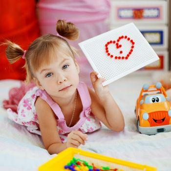 Child showing mosaic heart
