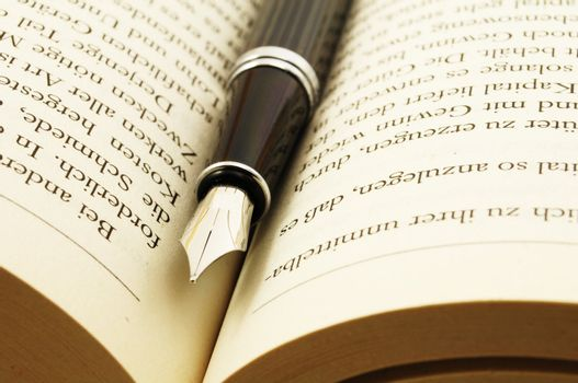 education or reading concept with book and pen