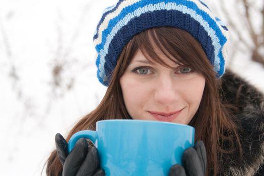 A beautiful young lady holding a large blue mug