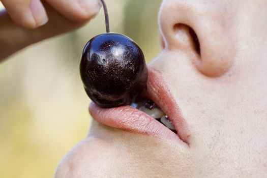 Close up view of a woman trying to eat a cherry.