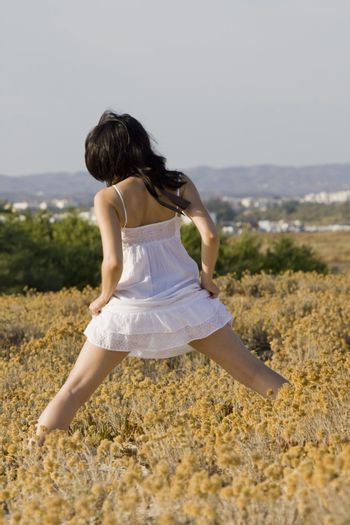 Young woman with white dress surrounded practicing yoga.