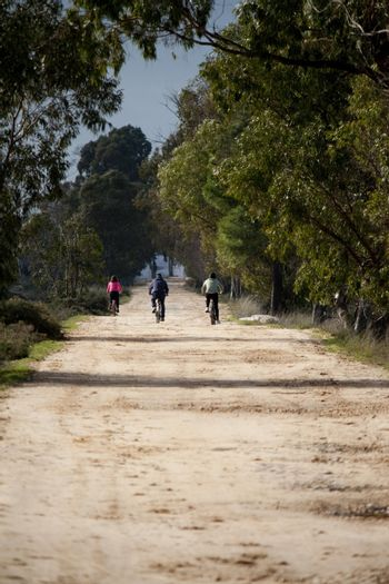 View of three persons riding a bike on a dirt road.