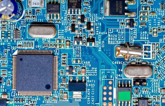 Close-up photograph of the microchips and micro-electronic components on a blue circuit board