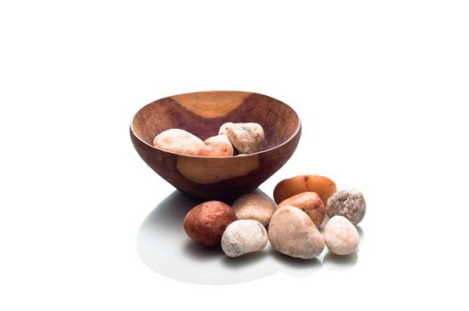 Small wooden bowl containing stones isolated on a white background