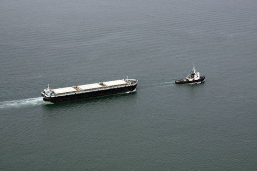Aerial view of a cargo transportation ship escorted by a small fishing boat.