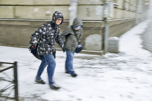 ST PETERSBURG, RUSSIA-FEBRUARY 15, 2008: Unidentified boys trying to break through heavy snowstorm and blizzard in city street