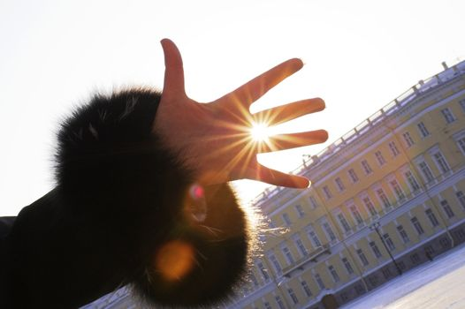 A girl wearing a winter coat shows her hand.