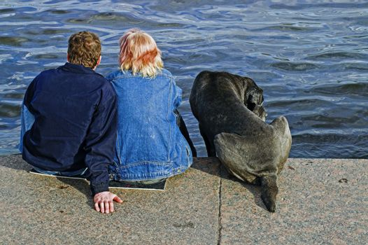 A couple and a dog sitting at the embankment of Neva river in Saint Petersburg, Russia.