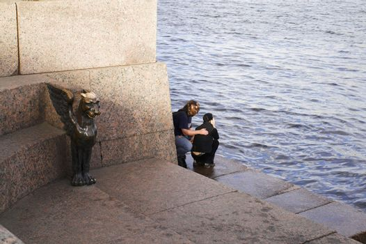 Couple sitting by river bank