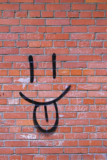 Smile Graffiti on a Red Brick Wall.
