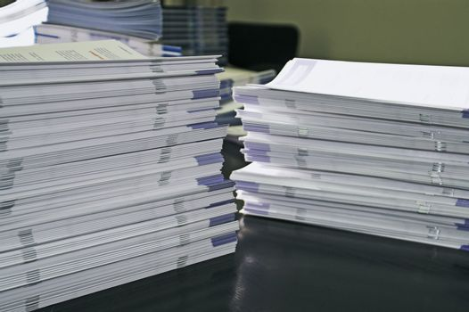 Piles of handout papers lying on table.